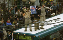 Two protestors stand atop a bus above a crowd in Seattle
