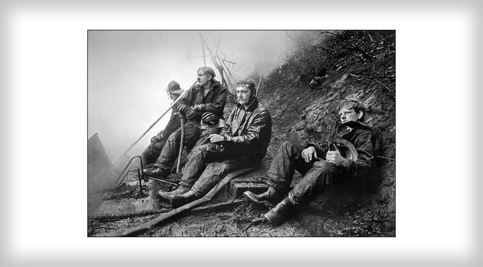 Four exhausted firemen looking despondent, sit on a gritty hillside in this Pulitzer Prize winning black and white photo, 'Lull in the Battle.'