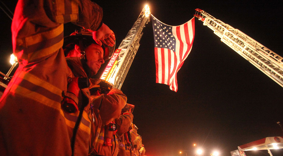 Against a background of 2 construction tower cranes supporting an American flag, a line of Central Pierce Fire and Rescue personnel salute as part of the procession that transported the bodies of four slain police officers from where they were killed in Parkland to the Pierce County Medical Examiner's Office in Tacoma.